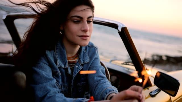 Frau-im-Cabrio-mit-Wunderkerzen-am-Strand-bei-Sonnenuntergang