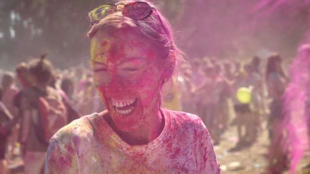 Young-happy-girl-in-colourful-powder-is-histerically-laughing-and-dancing-on-holi-festival-in-daytime-in-summer-watching-at-camera-color-concept-emotional-concept