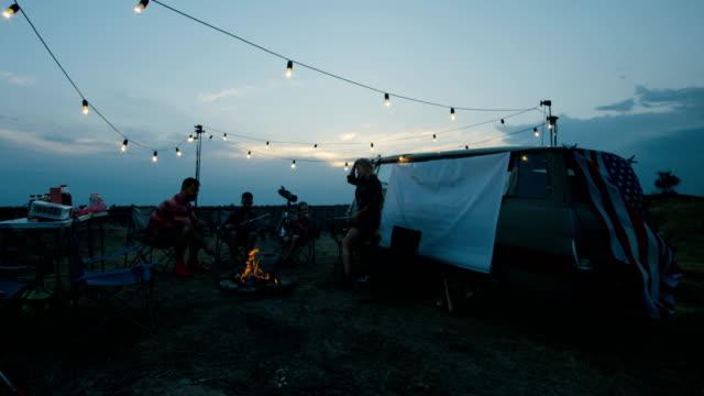 Laughing-family-frying-marshmellow-on-bonfire
