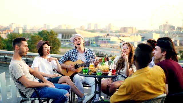 Grupo-multirracial-de-jóvenes-es-cantar-canción-sentado-en-círculo-en-el-techo-mientras-que-el-joven-es-tocar-la-guitarra-Mesa-con-alimentos-y-bebidas-y-bella-ciudad-es-visible-