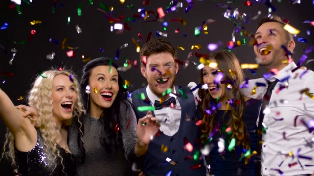 happy-friends-at-party-under-confetti-over-black