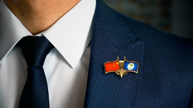 Businessman-Walking-Towards-Camera-With-Friend-Country-Flags-Pin-China---Belize