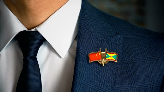 Businessman-Walking-Towards-Camera-With-Friend-Country-Flags-Pin-China---Grenada
