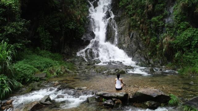 Meditación-de-mujer-yoga-asiático-cerca-de-cascada-en-las-montañas