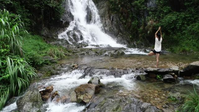 Vista-aérea-de-mujer-de-estilo-de-vida-saludable-haciendo-yoga-cerca-de-cascada-en-el-bosque