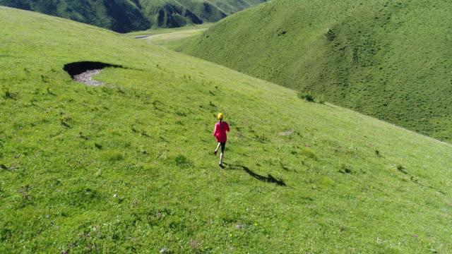 Vista-aérea-de-corredor-de-trail-de-mujer-fitness-joven-corriendo-encima-de-Prado-mountain-4k