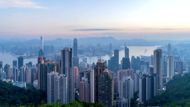 Time-lapse-Night-to-day-Hong-Kong-Downtown-and-Victoria-Harbour-Financial-district-in-smart-city-Skyscraper-and-high-rise-buildings-from-the-peak-Aerial-view-at-sunrise-