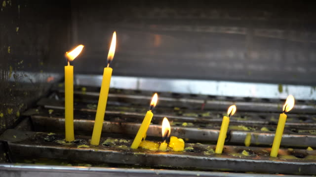 Burning-candle-light-in-front-of-Asian-temple---Faith-spirituality-and-religion-concept