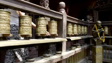 Woman-spins-prayer-wheels-in-Patan-Durbar-Square-Kathmandu-valley-Nepal-