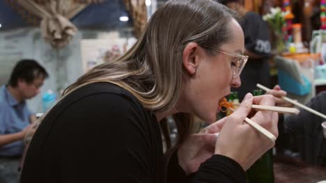 slow-motion-young-woman-in-glasses-enjoying-noodles-with-chopsticks-at-a-casual-restaurant