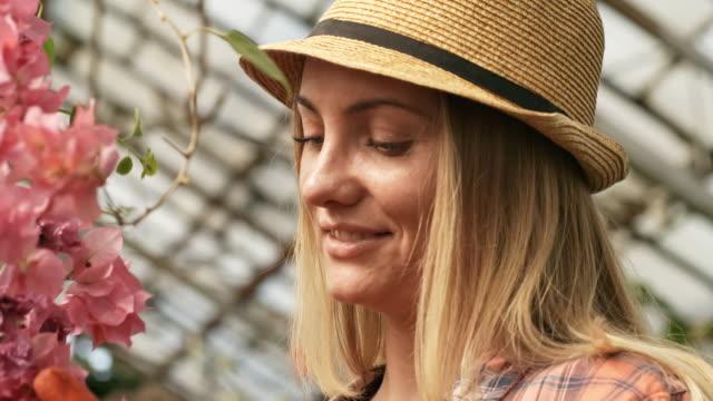 Mujer-mirando-flores-en-invernadero