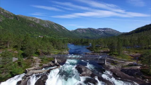 Young-girl-watching-waterfall-in-Norway
