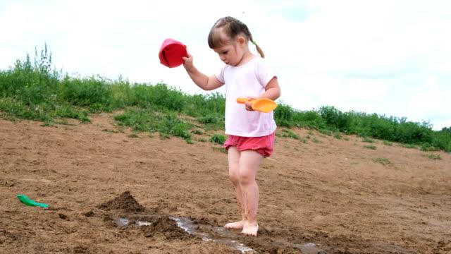 Kleines-Mädchen-gießt-Wasser-aus-einem-Eimer-in-den-Sand-Kinder-spielen-am-Strand
