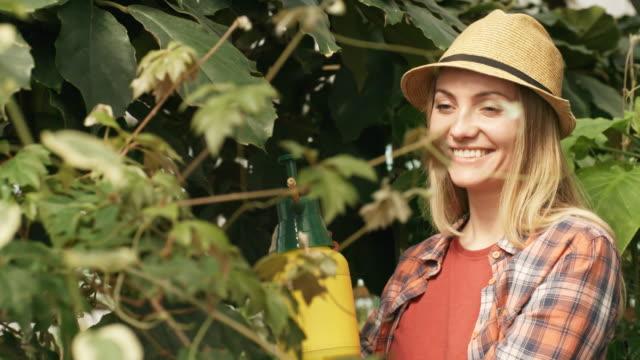 Mujer-feliz-rociando-las-plantas-en-invernadero