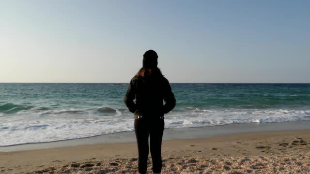 Niña-está-de-pie-en-la-orilla-del-mar-Mediterráneo-en-un-frío-día-de-otoño