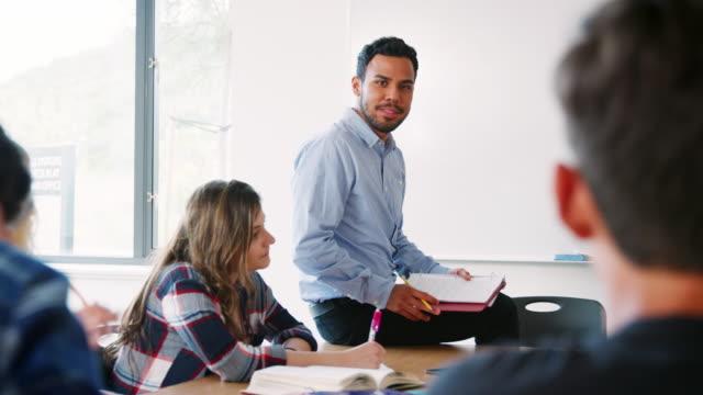 Tutor-de-secundaria-hombre-sentado-en-el-escritorio-docente-clase