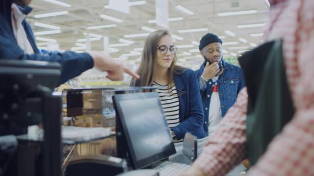 En-el-supermercado:-retirada-contador-cajero-escanea-Abarrotes-y-alimentos-Los-clientes-colocar-productos-en-la-línea-transportadora-Limpie-el-moderno-centro-comercial-