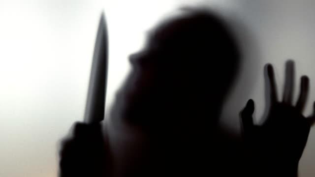Hombre-con-el-cuchillo-detrás-del-vidrio-esmerilado-de-4-k-lenta-60fps