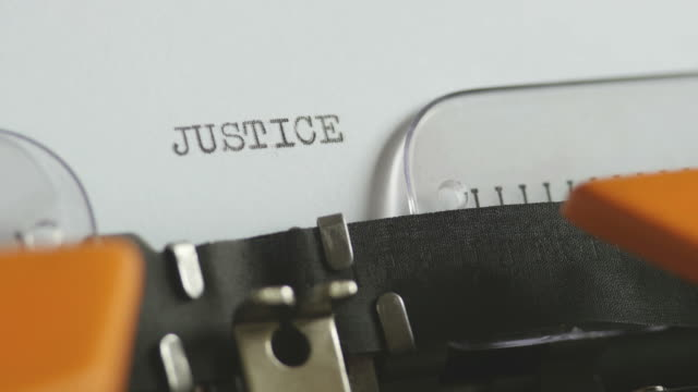 Close-up-footage-of-a-person-writing-JUSTICE-on-an-old-typewriter-with-sound