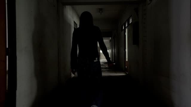Silhouette-eines-Mannes-tragen-ein-Messer-zu-Fuß-in-einem-verlassenen-Haus