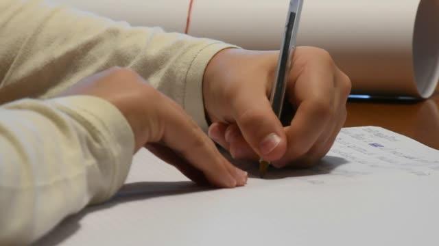 hand-of-left-handed-boy-writing-school-homework
