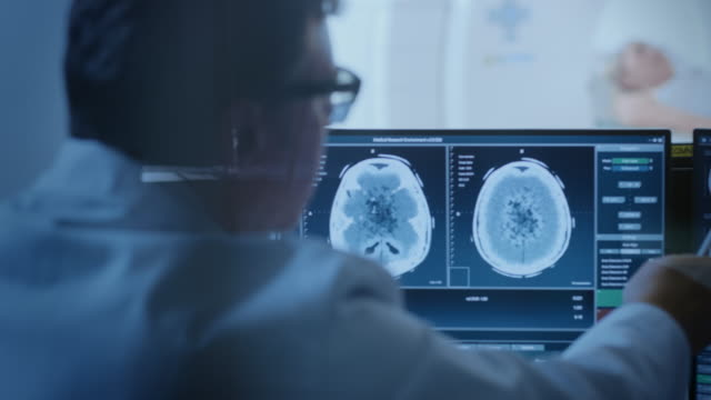 In-Medical-Laboratory-Patient-Undergoes-MRI-or-CT-Scan-Process-under-Supervision-of-Radiologist-in-Control-Room-He-Watches-Procedure-and-Monitors-Brain-Activity-Results-
