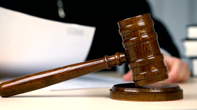 Judge-reading-and-signing-papers-in-courtroom-legal-system-justice-occupation