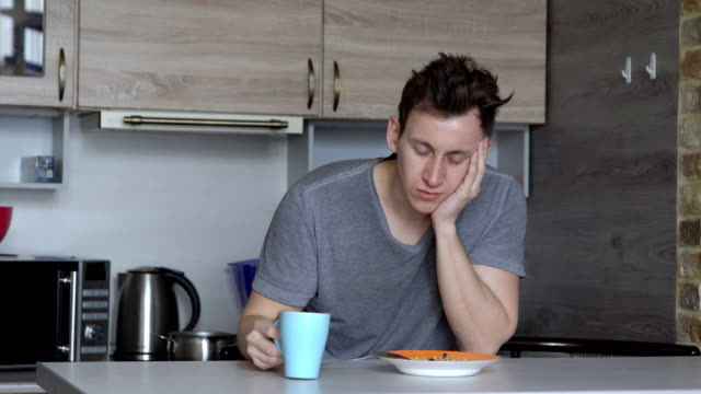 Man-falling-asleep-eats-oatmeal-and-coffee-in-the-kitchen
