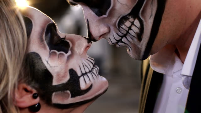 Halloween-loving-couple-with-skull-makeup-looking-at-each-other-