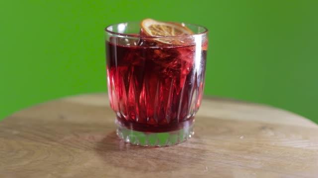Whiskeyglas-auf-grünem-Hintergrund-cocktail-dreht-auf-Hromokoy-Hintergrund-alkoholischen-Cocktail-auf-grünem-Hintergrund