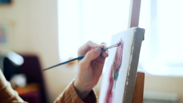 Joven-creativa-es-flores-de-pintura-sobre-lienzo-trabajando-en-taller-de-luz-solo-con-óleo-y-pincel-Arte-arte-pictórico-y-el-concepto-de-manía-
