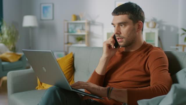 Hombre-guapo-sentado-en-el-sofá-en-casa-habla-en-el-teléfono-móvil-y-utiliza-el-ordenador-portátil-