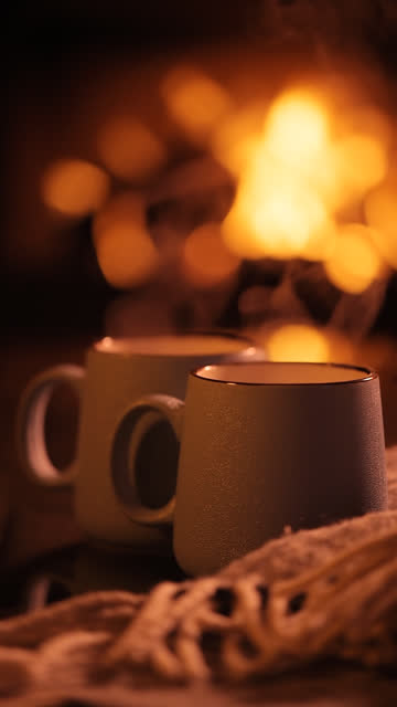 Vertical-video-Steam-from-a-cups-with-a-hot-cocoa-on-the-fireplace-background-
