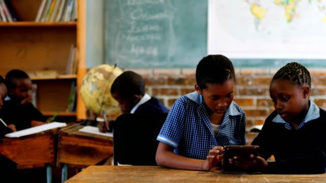 Profesor-con-tableta-digital-de-los-estudiantes-en-aula-4k