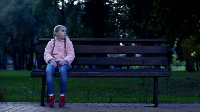 Sad-school-girl-sitting-on-bench-in-park-lost-missing-kid-waiting-for-parents