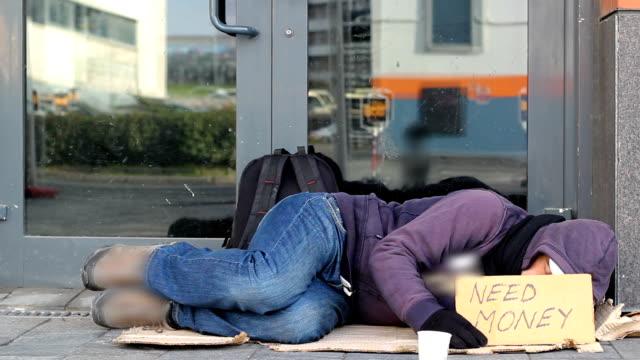 Homeless-beggar-man-sleeping-on-the-street