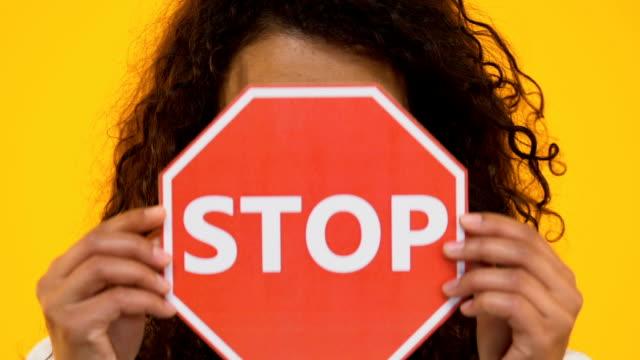 Biracial-girl-holding-stop-sign-protesting-bullying-or-racism-gun-violence