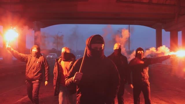 Grupo-de-hombres-jóvenes-en-pasamontañas-con-la-señal-ardiente-roja-de-la-llamarada-que-camina-en-el-camino-debajo-del-puente-cámara-lenta
