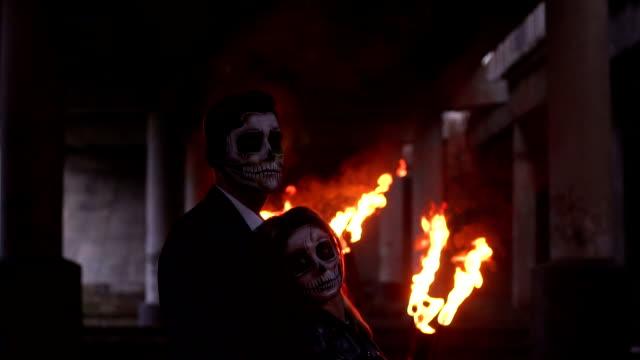 Pareja-con-maquillaje-de-cráneo-en-el-fondo-de-fuego-ardiente-y-humo-Víspera-de-Todos-los-Santos