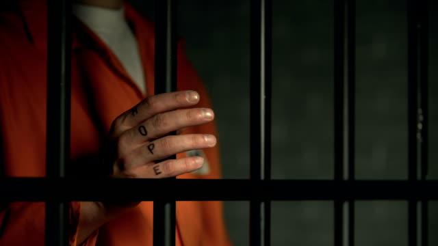 Esperanza-en-el-hombre-encarcelado-dedos-sosteniendo-rejas-soñar-con-la-libertad