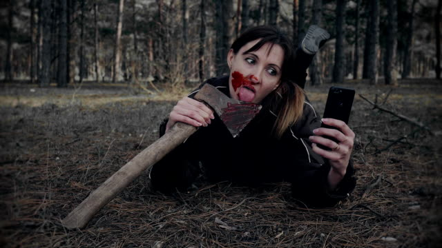 Woman-with-bloody-makeup-makes-funny-selfies-on-mobile-phone-for-social-networks-on-Halloween-in-forest