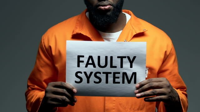 Faulty-system-phrase-on-cardboard-in-hands-of-Afro-American-prisoner-disorder