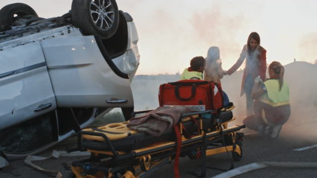 Burning-Rollover-Car-in-a-Crash-Traffic-Accident:-Team-of-Paramedics-Perform-Emergency-First-Aid-to-Injured-Mother-and-Young-Daughter-Giving-Oxygen-Mask-and-Checking-for-Trauma