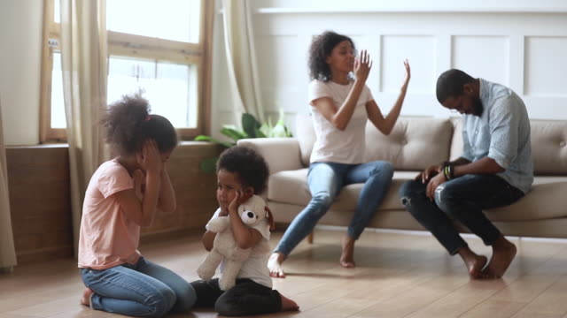 Niños-africanos-cerrando-los-oídos-molestos-por-los-padres-que-luchan-en-casa