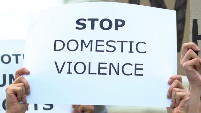 Banner-con-lema-Detener-la-violencia-doméstica-en-manos-activistas-manifestación-contra-el-abuso