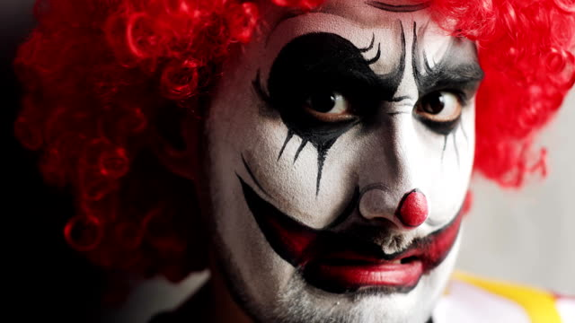Portrait-of-sad-and-evil-smiling-scary-clown-on-Halloween-looking-at-camera