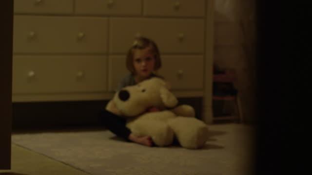 Niña-triste-se-sienta-en-su-piso-del-dormitorio-solo-con-un-animal-de-peluche