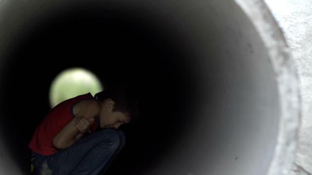 muchacho-solitario-sin-hogar-escondido-dentro-de-un-túnel-de-drenaje-de-la-helada-tratando-de-mantener-caliente