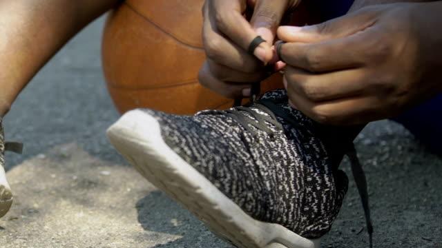 Afroamericana-del-Baloncestista-atar-sus-cordones-antes-del-partido-de-cerca