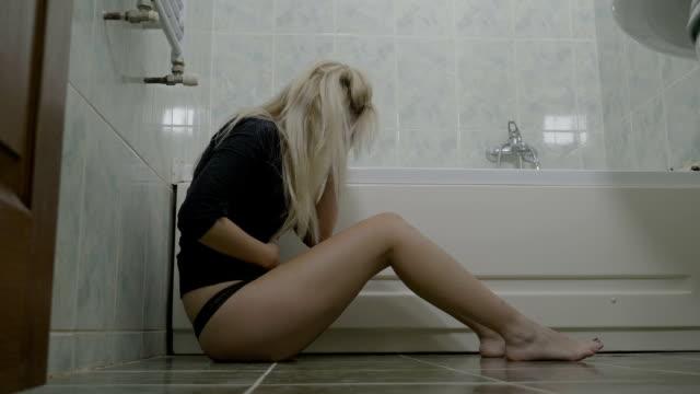 Triste-sexy-atractiva-joven-mujer-rubia-sentada-en-el-suelo-del-baño-y-llorando-después-de-perder-el-embarazo